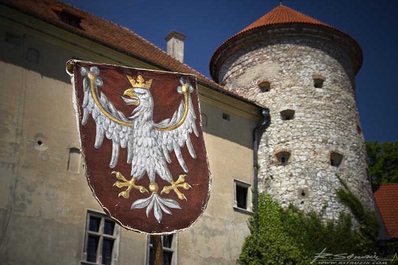 Pieskowa Skała, stylizowane godło na tle wieży zachodniej.